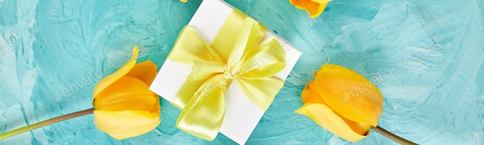 Banner of Gift box with yellow ribbon near tulip