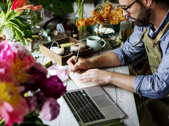 Man flower shop owner writing note on the table