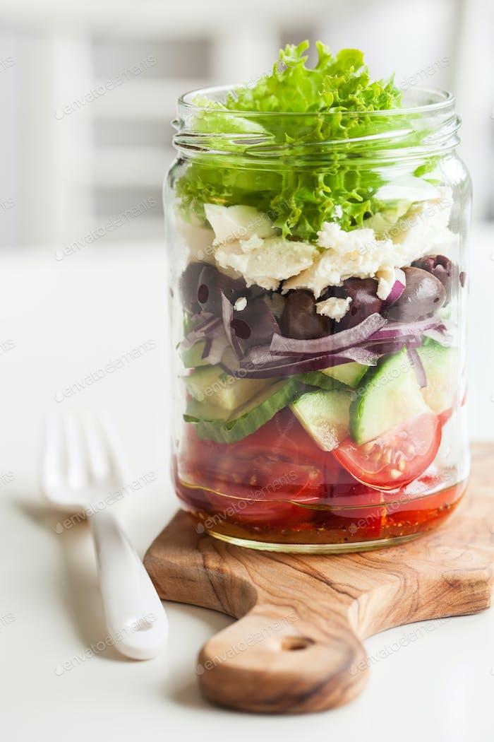healthy greek salad in mason jar. tomato olive feta onion