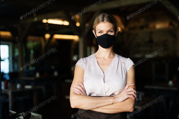 Waitress with face mask standing indoors on terrace restaurant, arms crossed