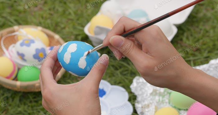 Drawing on egg for Easter holiday at outdoor green park
