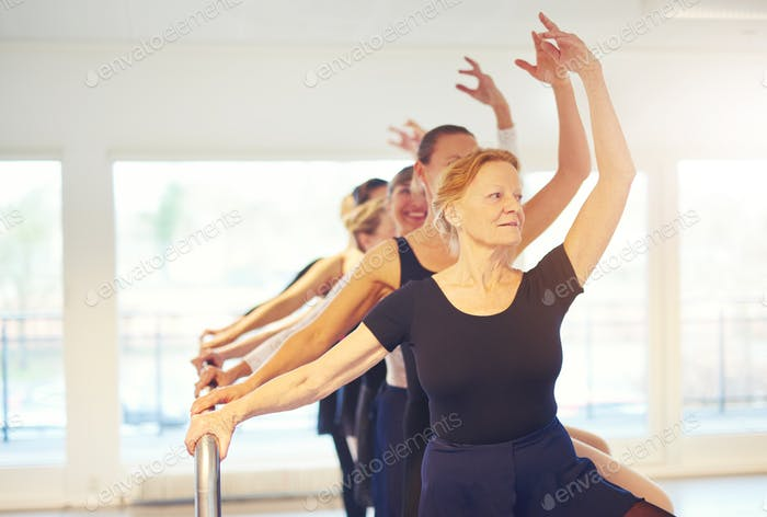 Group of adult ballet dancers with hands up in class
