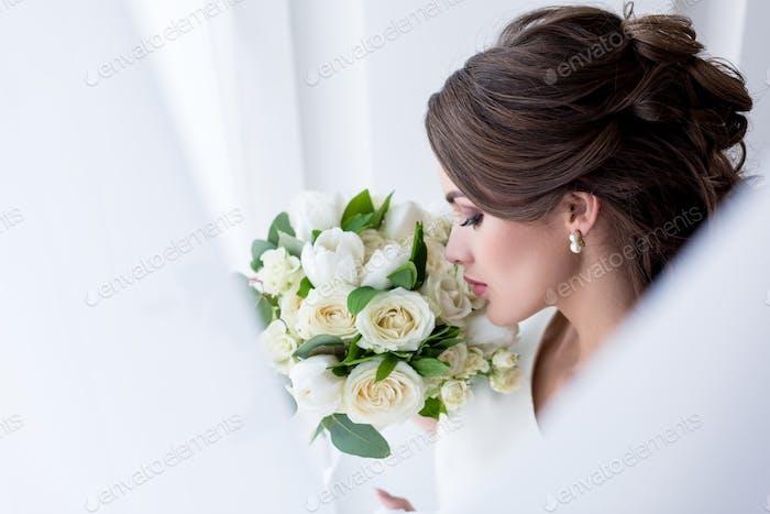 attractive brunette bride sniffing wedding bouquet