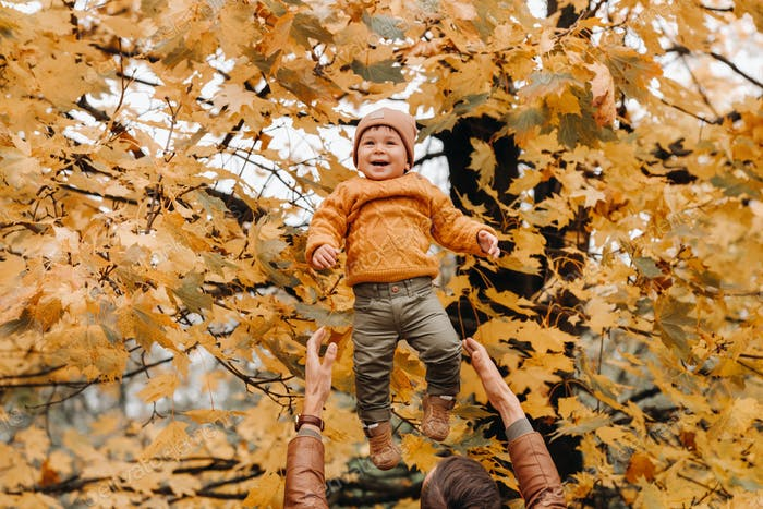 a father throws a child against the background of autumn leaves in the Park. dad throws up his son