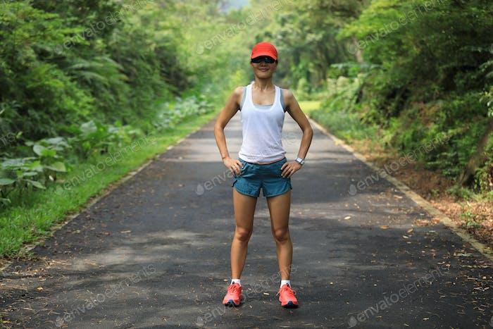 Fitness woman runner relaxing on park trail