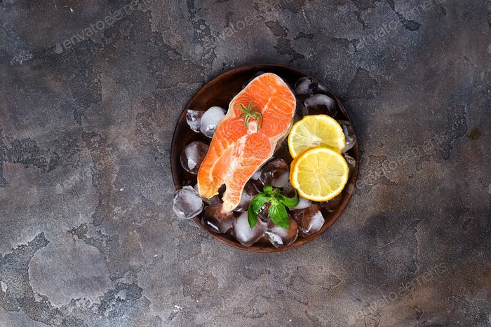 Salmon steaks on ice withlemon slice on wooden plate
