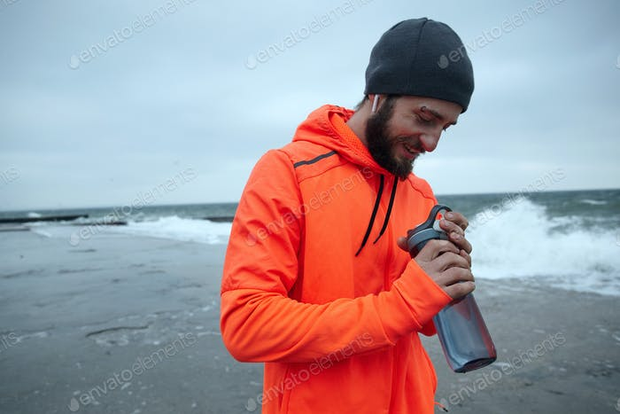 dark haired bearded man goes in for sport every morning, going along seafront with fitness bottle