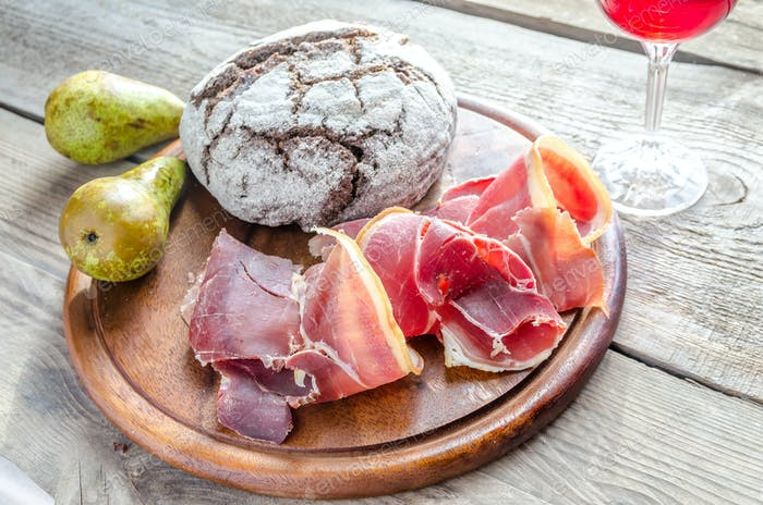 Slices of italian ham with glass of wine on the wooden board