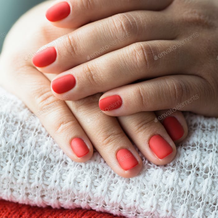 Closeup photo of a beautiful female hands with red nails