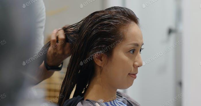 Asian woman with moisture hair treatment in beauty salon