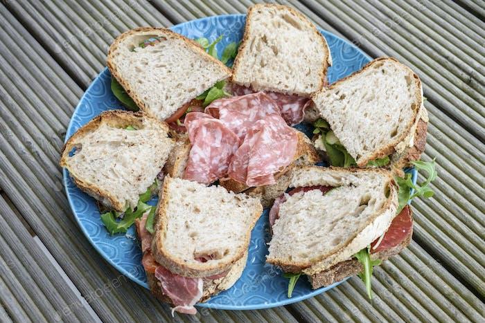 Hohe Winkel Nahaufnahme der Auswahl von Sandwiches mit Coppa und Salami auf einem blauen Teller.