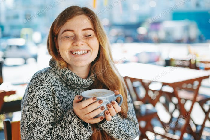 Woman holding coffee with hands while keeping eyes closed and sh