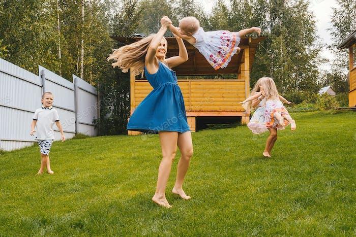 Счастливые дети и мама играют в саду