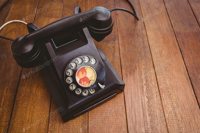 Blick auf ein altes Telefon auf Holzschreibtisch