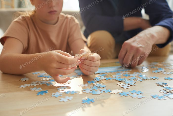 Girl Assembling Puzzle Close Up