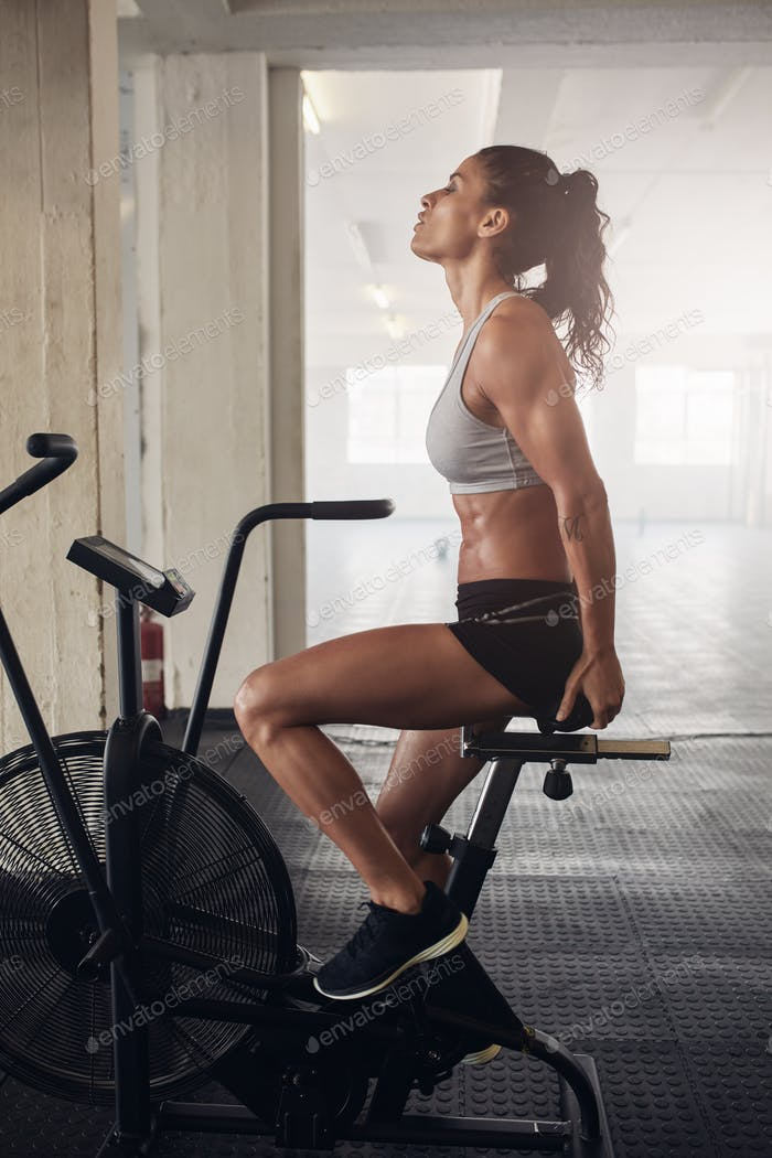 Female exercising on bicycle in health club