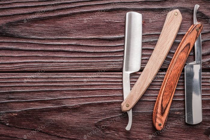 Vintage barber shop straight razor tool on wooden background