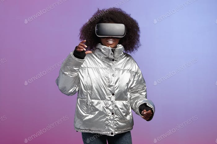 Trendy curly brown-haired girl dressed in a silver-colored jacket uses the virtual reality glasses