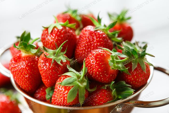 Ripe fresh strawberries in metal bowl closeup