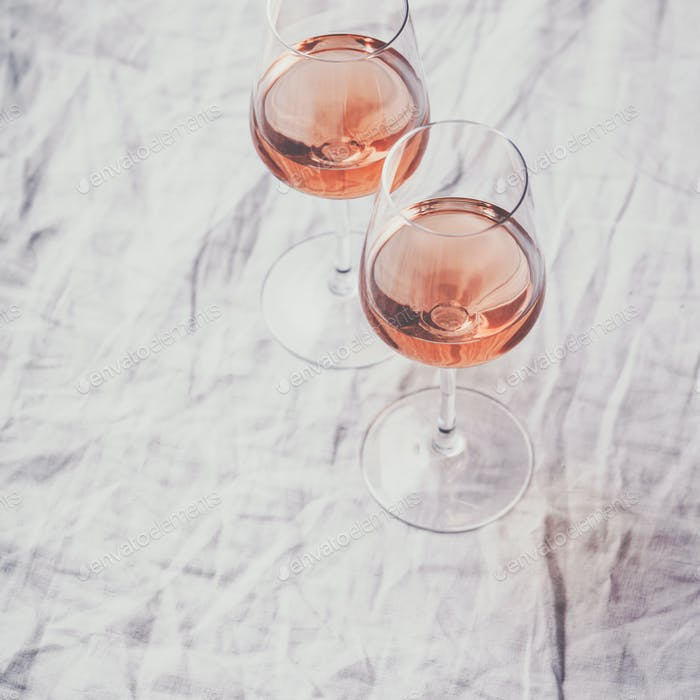 Rose wine in glasses on white linen cloth, flat lay