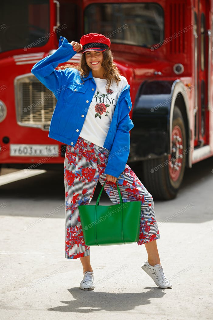 Stylish brunette girl dressed in white t-shirt, blue jacket, multi-colored pants and red cap poses