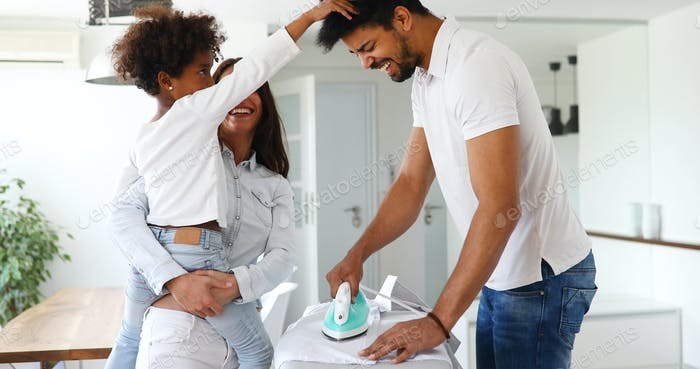 Young couple at home doing hosehold chores and ironing