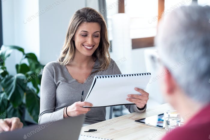 Smiling business woman reviewing her notes for meeting on coworking space.