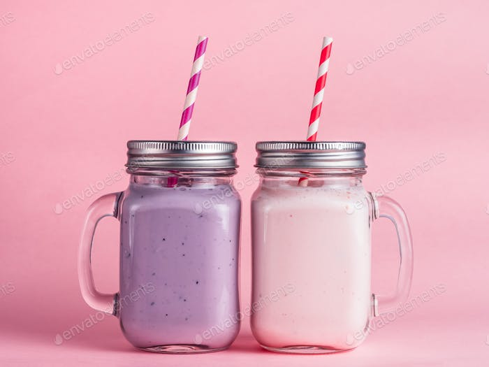 Strawberry and blueberry smoothie on pink