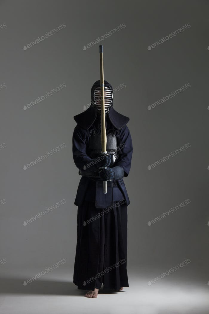 male in tradition kendo armor with shinai .
