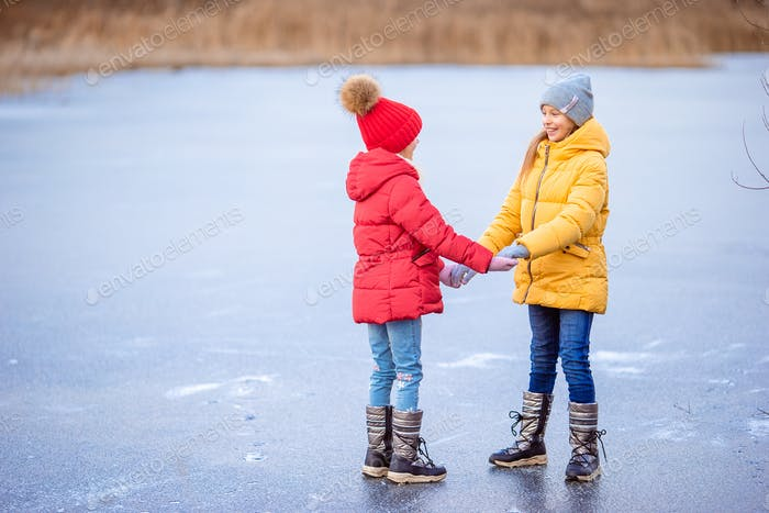 Adorable little girls skating on the ice-rink