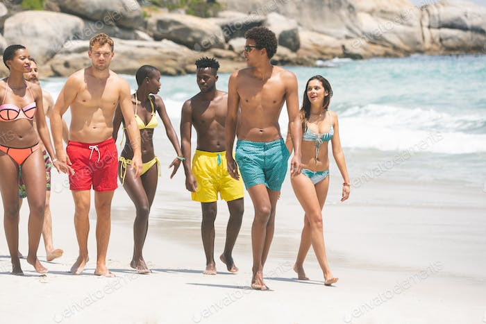 Group of diverse friends interacting with each other while walking at beach on a sunny day