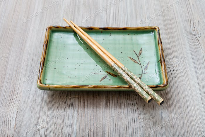 square plate with chopsticks on gray table