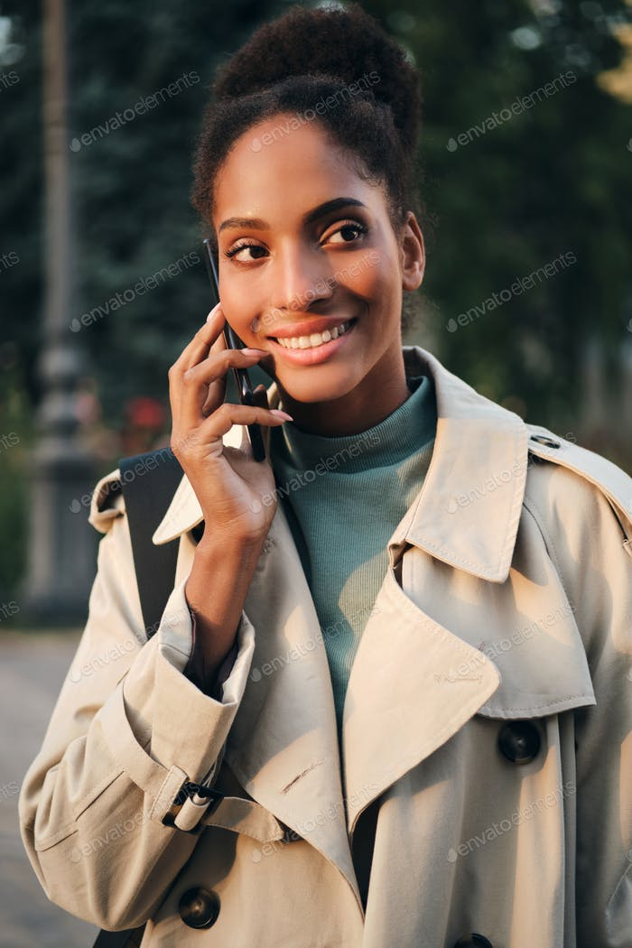 Beautiful smiling casual African American girl in trench coat happily talking on cellphone outdoor