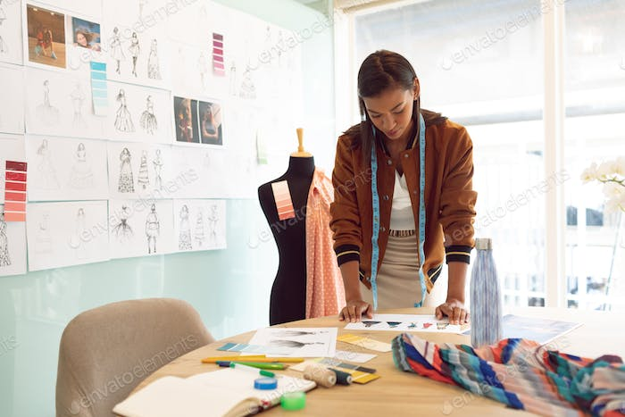 Beautiful Mixed Race Female Fashion Designer Looking At Sketches On Table Photo By Wavebreakmedia On Envato Elements
