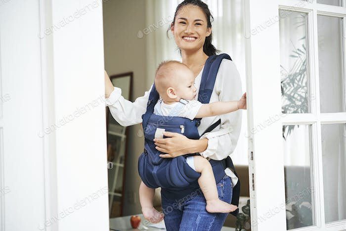 Cheerful mother opening front door