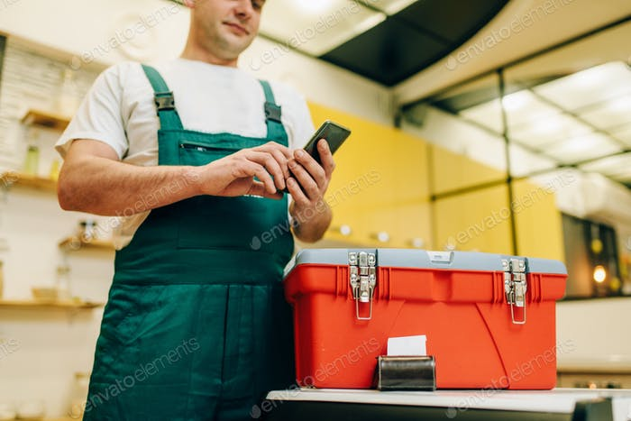 Repairman in uniform holds phone against toolbox