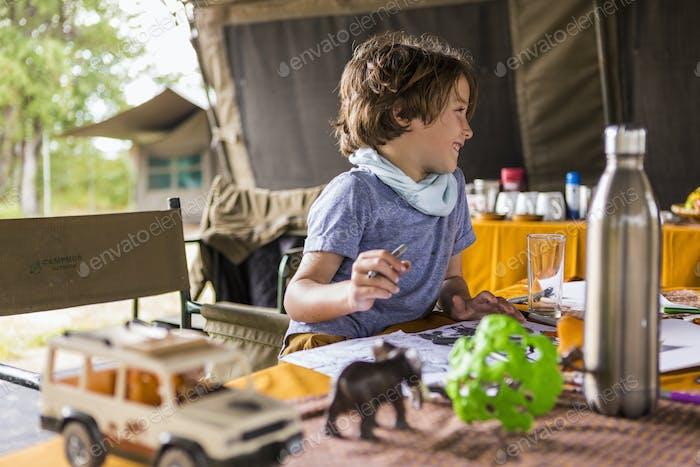 Lächelnder Junge, Profil, in einem Zelt-Camp, auf Safari, spielen mit Safari-Tierspielzeug.