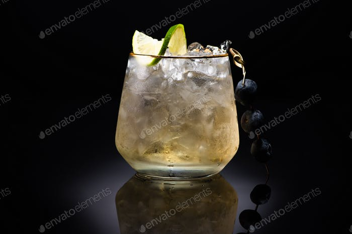 Transparent Glass With Ice And Golden Liquid Garnished With Lime And Blueberries on Black Background