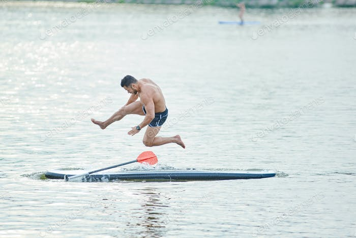 Sportsman jumping from sup board in lake's water