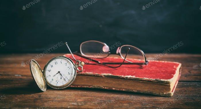 Vintage book and pocket watch on dark background