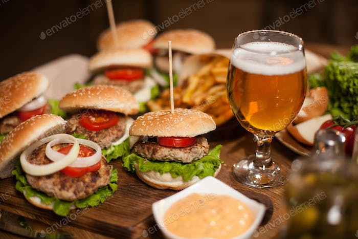 Ice cold beer with delicious burgers on a restaurant table