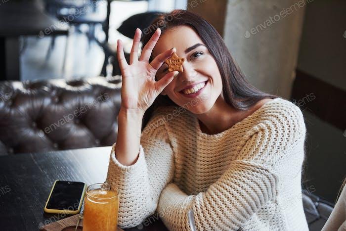 Nettes junges brünettes Mädchen hält den Keks in Form von Stern