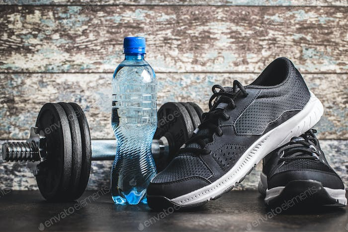 Fitness concept. Black sports shoes, dumbbell and bottle of water.