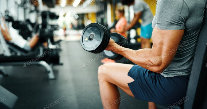 Muscular bodybuilder guy doing exercises in gym