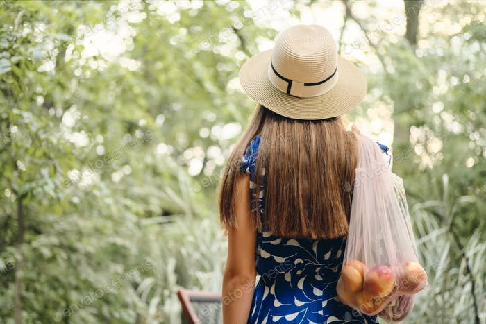 Back view of young brown haired woman in dress and hat holding eco bag with fruits and vegetables