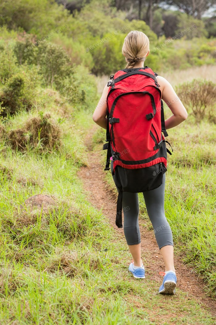 Blonde hiker hiking with backpack in the nature