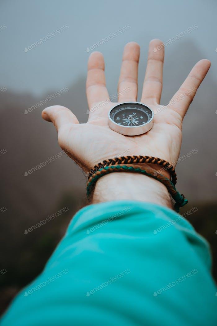 Gestreckter Mann Arm mit Kompass auf der Handfläche gerichtet auf Berggipfel an bewölkten Tag