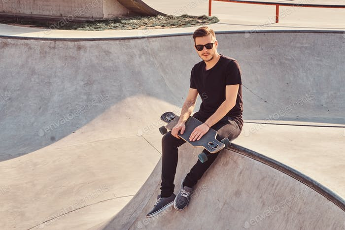 Stylish hipster in sunglasses dressed in black jeans and shirt holds skateboard
