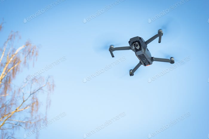 Drone flying in the blue sky, unmanned copter flight