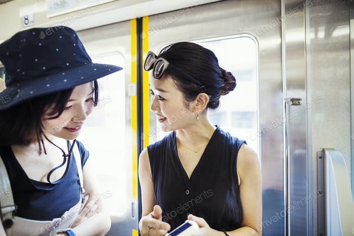 Two young woman traveling on a train.